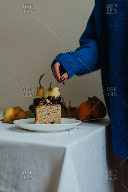 Sliced of a cake topped with pears and chocolate sauce