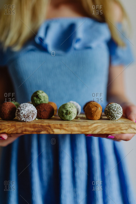 Woman holding wood board with various cookie bites