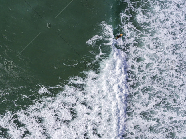 Aerial view of a surfer riding a wave