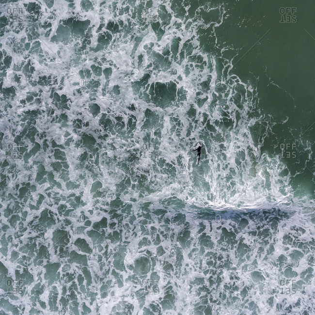 Aerial view of a surfer paddling on a surfboard