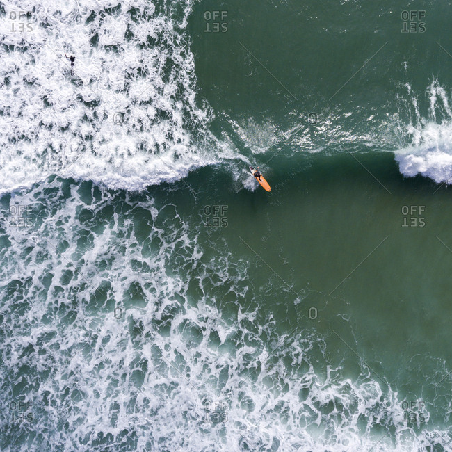 Surfer riding a wave from above