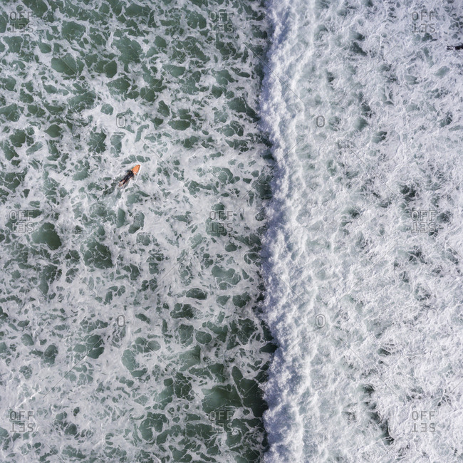 Surfer paddling on a surfboard in the ocean