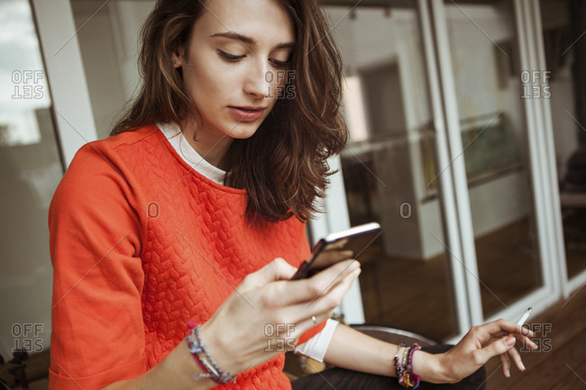 Young woman checking smartphone on balcony smoking a cigarette