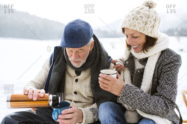 Senior couple having a break with hot beverages in snow-covered winter landscape