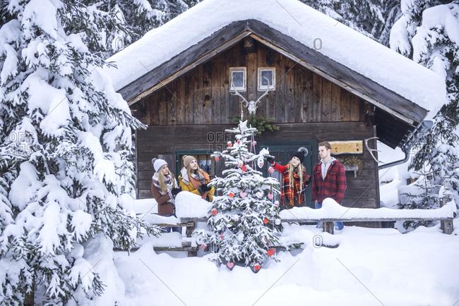 Austria- Altenmarkt-Zauchensee- friends decorating Christmas tree at wooden house