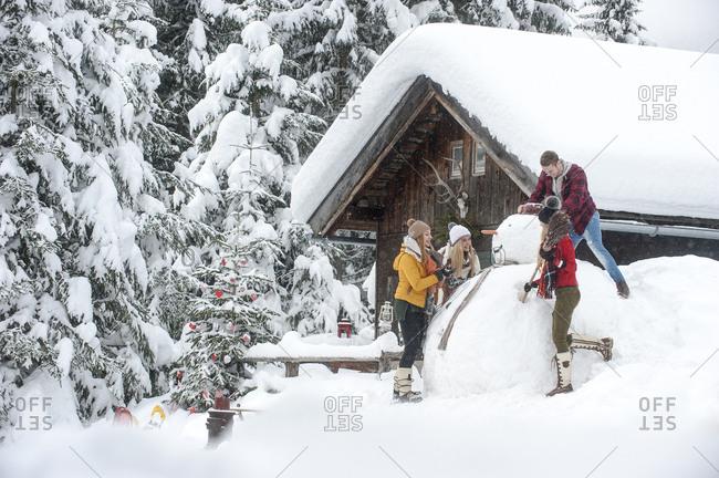 Austria- Altenmarkt-Zauchensee- friends building up big snowman at wooden house