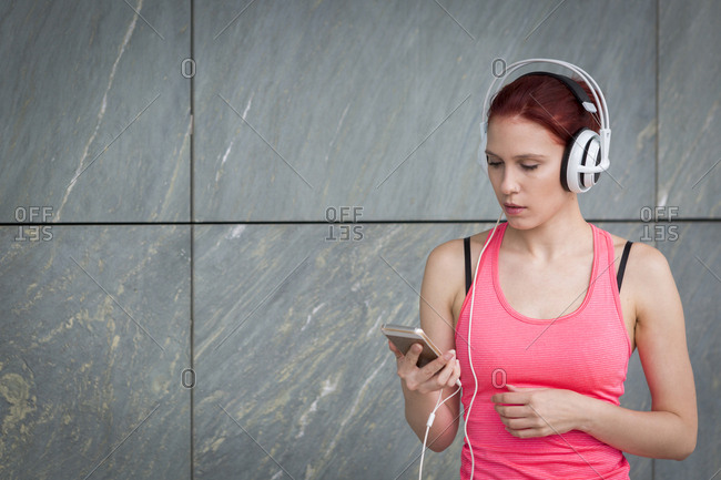Woman in sports outfit wearing headphones- listening music