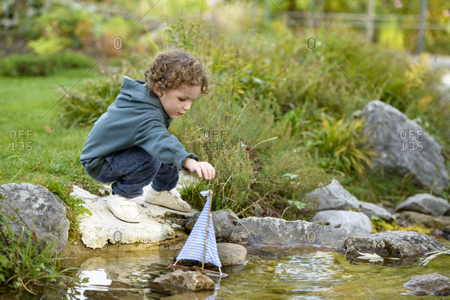 Toddler playing with a toy boat in a brook