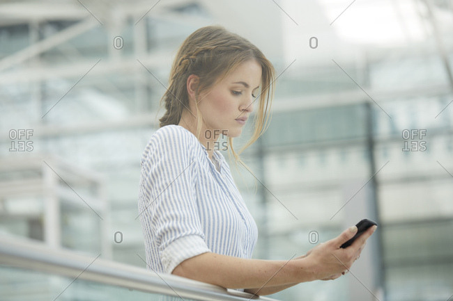 Serious woman checking her cell phone