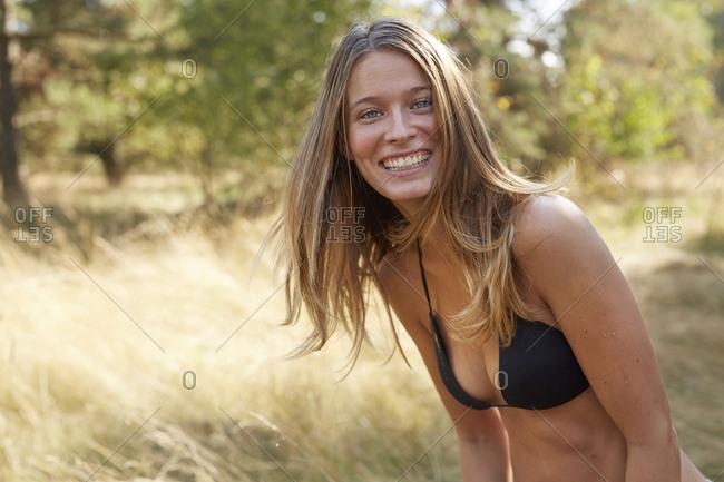 Portrait of laughing young woman wearing bikini top in nature