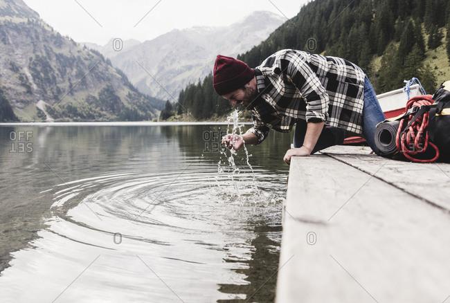 Austria- Tyrol- Alps- man kneeling on jetty refreshing at mountain lake