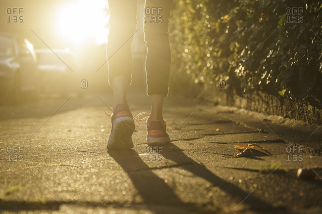 Legs of woman jogging on walkway at sunset