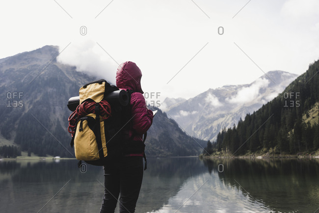 Austria- Tyrol- Alps- hiker standing at mountain lake