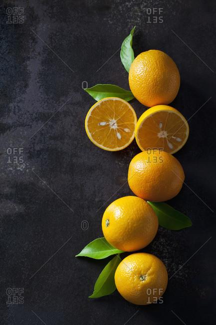 Organic oranges in halves on dark background