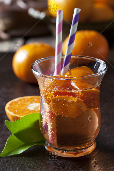 Fruit spritzer of tangerines in a glass with drinking straws