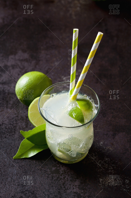 Fruit spritzer of limes in a glass with drinking straws