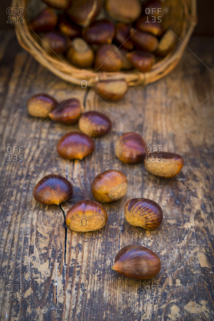Roasted sweet chestnuts in a basket and on wood