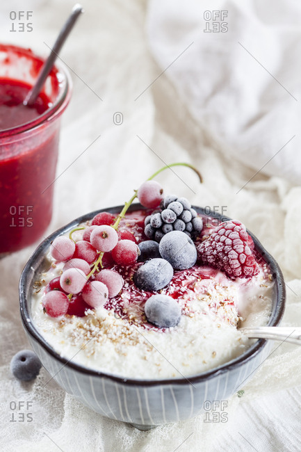 Bowl of natural yoghurt with raspberry sauce and frozen fruits