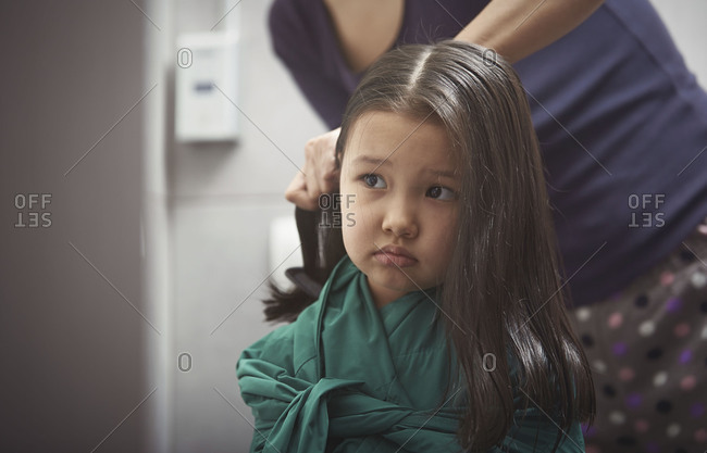 Girl looking in mirror as mother styles her hair