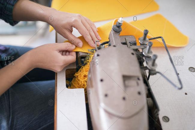 Seamstress sewing yellow fabric on a sewing machine