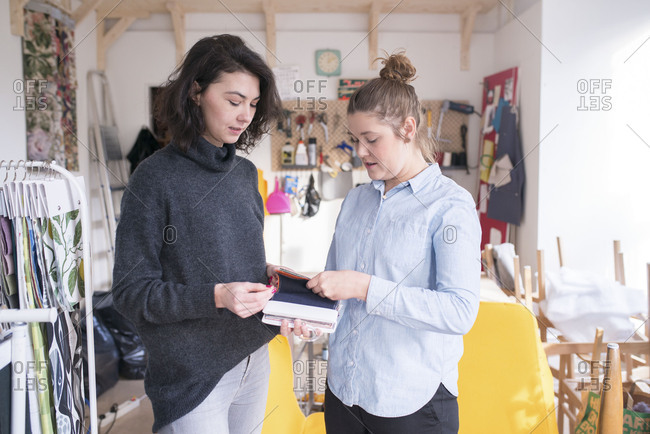 Two fashion designers looking through book of fabric swatches