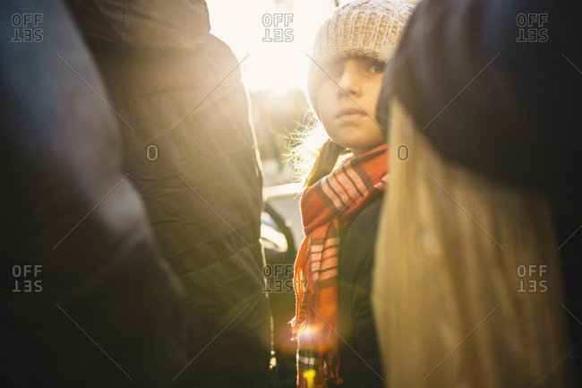 Girl wearing knit hat and scarf looking back at camera with lens flare