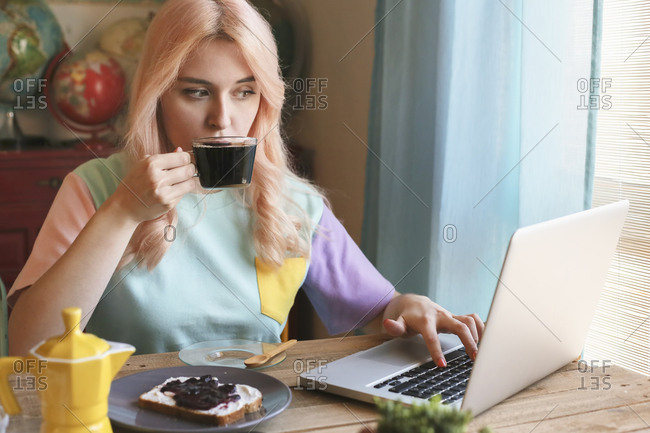 Young woman having breakfast and using laptop at home
