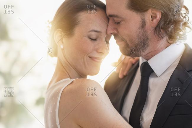 Bride and groom dancing cheek to cheek