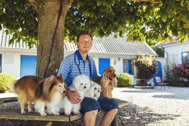 Portrait of man with four dogs