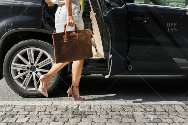Low section of woman getting into car