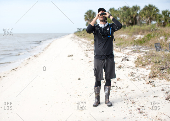 Man standing on beach, looking through binoculars, front view