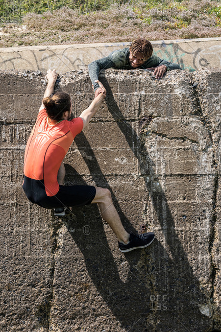 Young male free climber at top of sea wall helping friend climb up