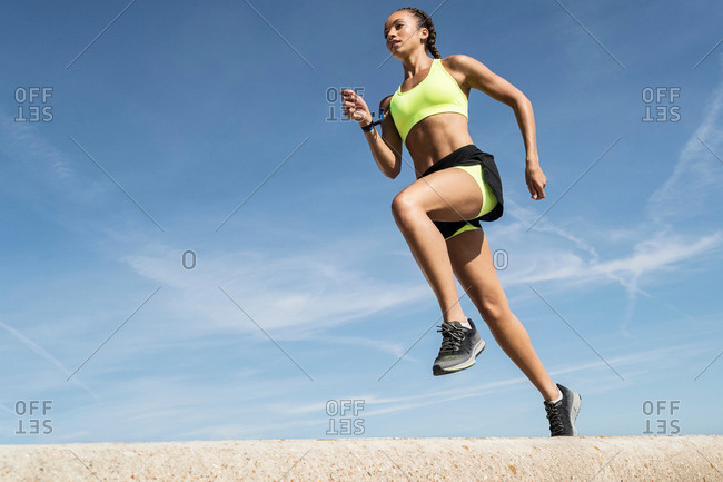 Low angle view of young female runner running along sea wall against blue sky