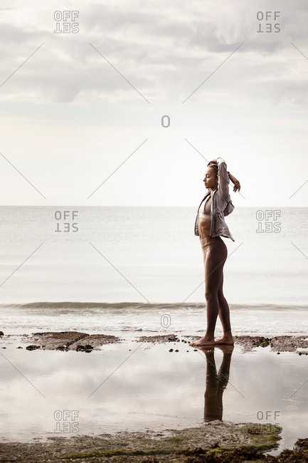 Young female runner at water's edge on beach stretching arms