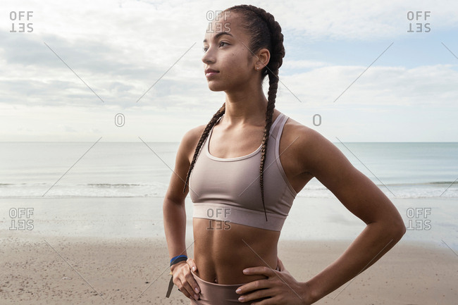 Young female runner with hands on her hips at beach