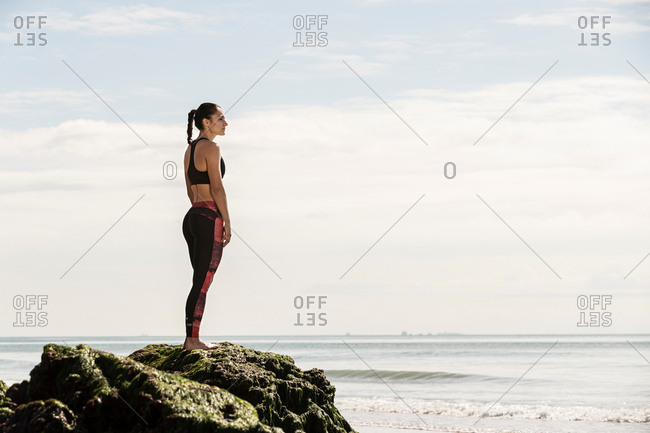 Young female runner looking out at sea from beach rock