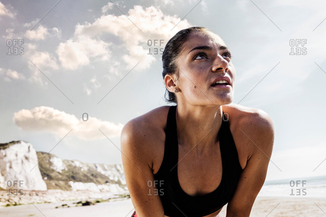 Exhausted young female runner taking a break on beach