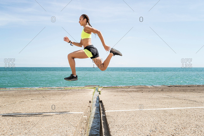 Young woman running outdoors, jumping over gap in bridge, mid air