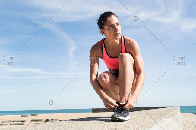 Young woman on sea wall, tying shoelace