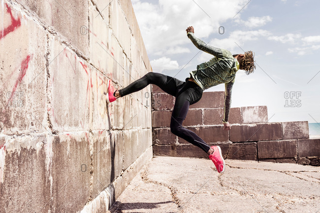 Young man, free running, outdoors, running up side of wall
