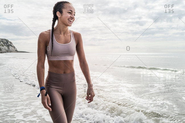 Young woman walking in sea, smiling