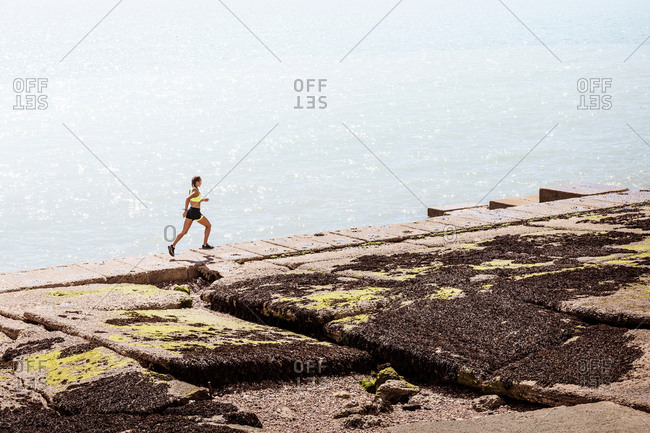 Young woman running along sea wall