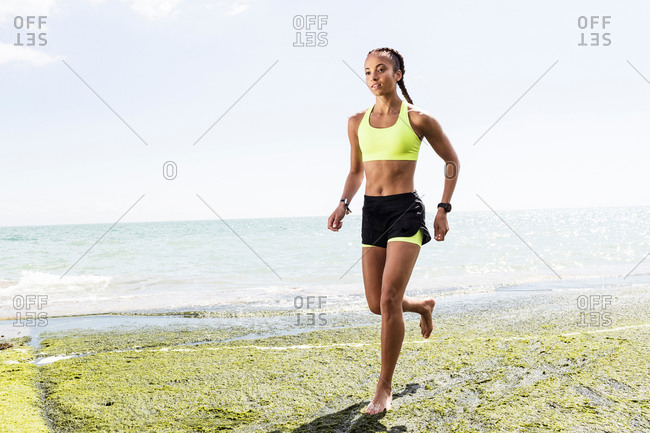 Young woman running, barefoot, beside sea