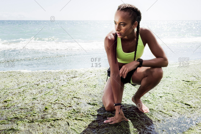 Young woman wearing sports clothing, crouching on beach