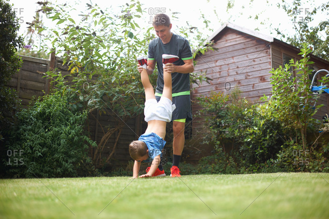 Father and son in garden, son's hands on grass, father lifting his legs
