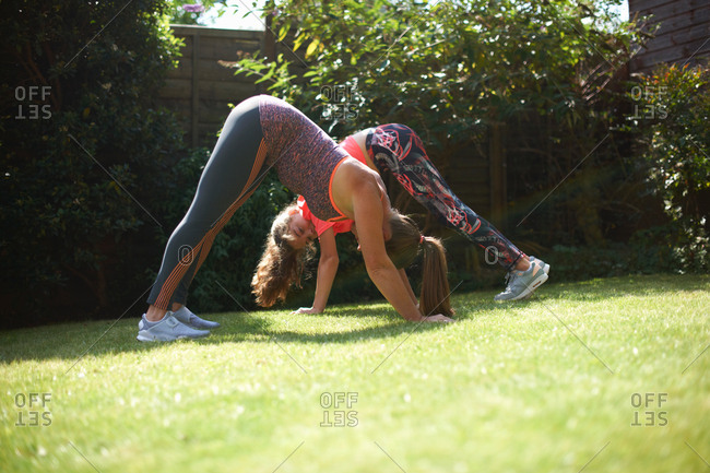 Mother and daughter exercising in garden, in yoga position
