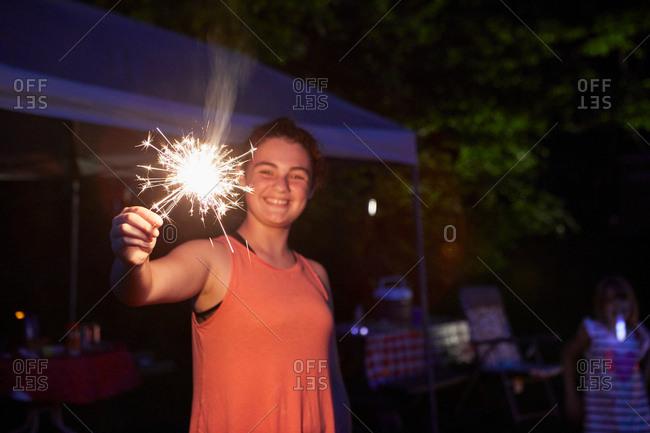 Girl outside at night, using sparkler