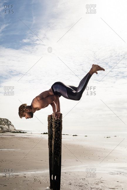 Young man training, doing handstand with raised legs on wooden beach posts