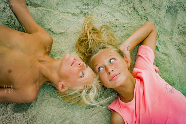Overhead portrait of blond brother and sister lying opposite each other on beach