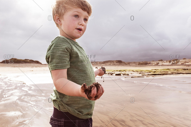 Young boy on beach, holding wet sand, Santa Cruz de Tenerife, Canary Islands, Spain, Europe